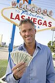 Mid-adult man holding notes in front of Welcome to Las Vegas sign ...